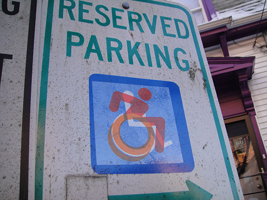 This header photo shows the earliest street-art version of the icon: a clear-backed sticker with an orange and red wheelchair-riding icon, superimposed over a blue and white standard icon. Old and new together.